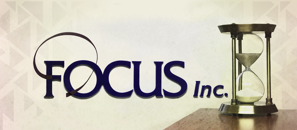 The Focus Inc. logo on a textured beige background, next to a fancy metal hourglass sitting on a table