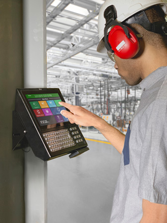 Tempus Pro Data Collection Device being used by an employee in an industrial factory, displaying options for clocking in and out