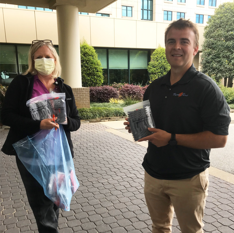 A Focus Inc employee delivers bags of 3D-printed face mask extenders to a local hospital representative