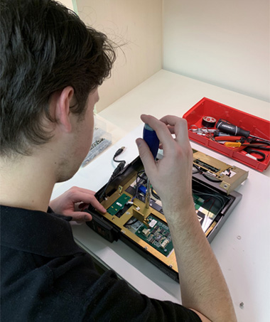 A Focus Inc employee using a socket wrench to perform hardware maintenance on a Tempus Pro device